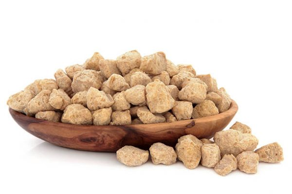 Soybean protein chunks in an olive wood bowl over white background.